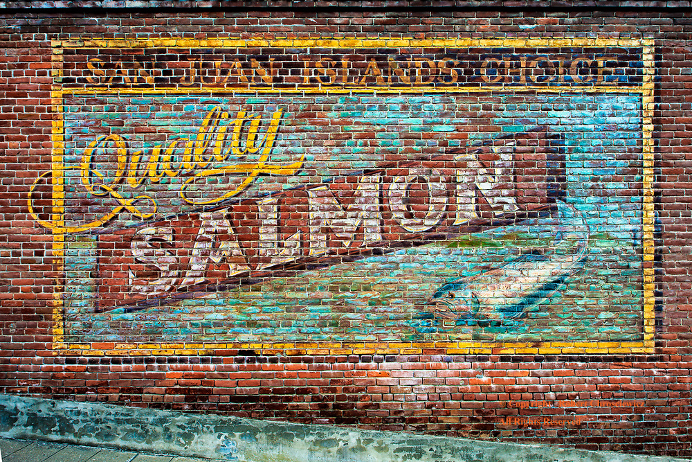 Salmon Ad: A very colourfully painted, yet somewhat faded, brick wall depicting Quality Salmon, which was once used in the making of a movie at this interior mountainous site in Greenwood, British Columbia Canada.