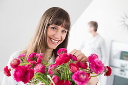 Portrait of woman with bouquet of pink flowers while man in background