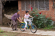 Wu Xianglian, 61 helps a neighbor girl learn to ride her grandson's new bicycle in the courtyard of the Cui family home. (Supporting image from the project Hungry Planet: What the World Eats.) The Cui family of Weitaiwu village, Beijing Province, China, is one of the thirty families featured, with a weeks' worth of food, in the book Hungry Planet: What the World Eats.