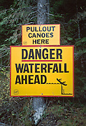 """""""Pull out canoes here - Danger ... Waterfall ahead"""" sign at Bowron Lake Provincial Park, British Columbia, Canada. On the 73-mile Bowron canoeing trip, paddle a rectangular circuit of wilderness lakes and portage your canoe rolled on wheels. The Cariboo Mountains are the northernmost subrange of the Columbia Mountains."""