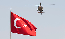"© licensed to London News Pictures. London, UK 30/08/2011. A Turkish Airforce helicopter goes past a Turkish flag at the 30th August Turkish Victory Day celebrations in capital Ankara on 30/08/12. Today the Syrian military has said it shot down a F-4 Phantom Turkish plane ""flying in airspace over Syrian waters"". Two crew members are being searched over Mediterranean sea. Photo credit: Tolga Akmen/LNP"