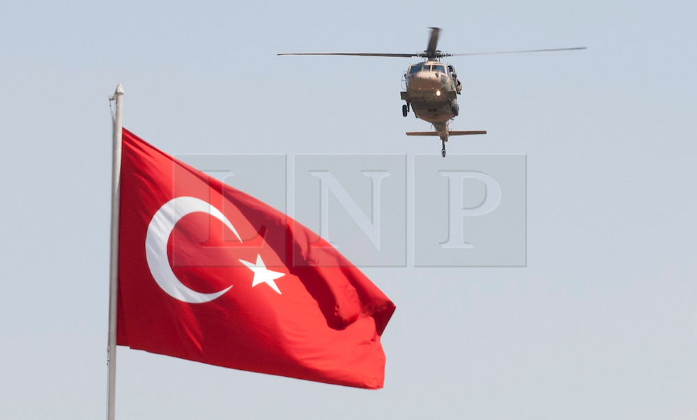 """© licensed to London News Pictures. London, UK 30/08/2011. A Turkish Airforce helicopter goes past a Turkish flag at the 30th August Turkish Victory Day celebrations in capital Ankara on 30/08/12. Today the Syrian military has said it shot down a F-4 Phantom Turkish plane """"flying in airspace over Syrian waters"""". Two crew members are being searched over Mediterranean sea. Photo credit: Tolga Akmen/LNP"""