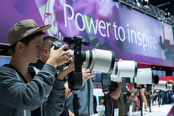 Visitors to the Canon stand try out a selection of large telephoto lenses on the opening day of bi-annual Photokina photography and imaging trade fair held in Cologne Germany; Tuesday 18 September 2012