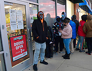 J. Jones of East St. Louis (left) said he got in line at this Game Stop store in Fairview Heights at midnight on Sunday so he could be sure of getting the new Playstation 4 video game console for his ten-year old daughter. Other Christmas shoppers queue up behind him in this photo taken shortly before the store was scheduled to open at 7 a.m. on Friday November 27, 2020. <br /> Photo by Tim Vizer