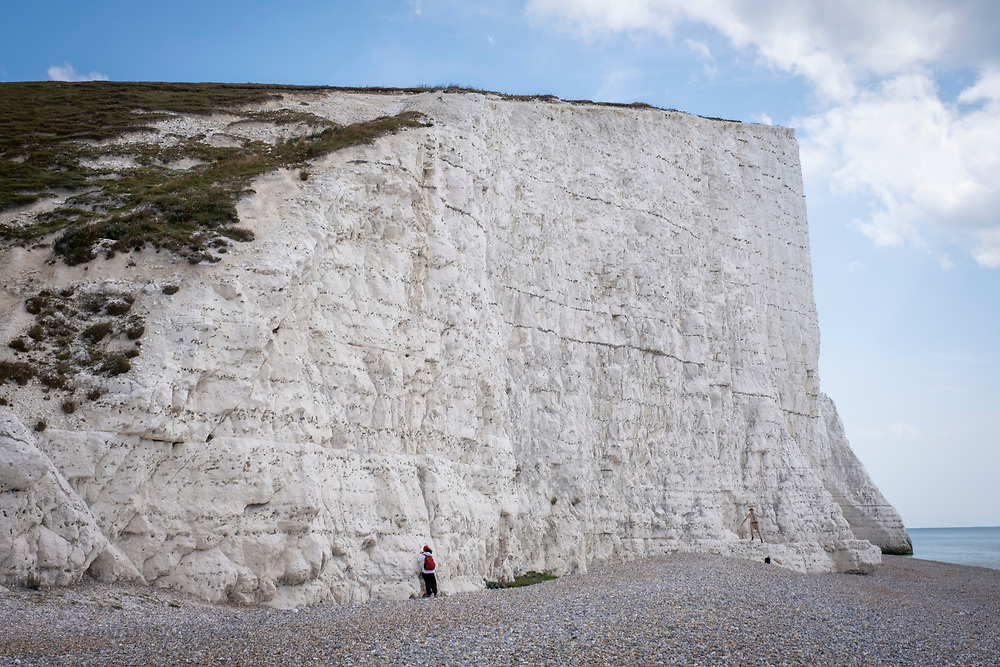 Tourists on Cuckmere Haven beach stand very close to the cliff edge of Seven Sisters Cliffs on the 25th of August 2021 near Seaford, East Sussex, United Kingdom. The Seven Sisters are a series of chalk cliffs by the English Channel. They form part of the South Downs in East Sussex, between the towns of Seaford and Eastbourne in southern England. Cliff falls are common along these cliffs as they are formed from chalk. (photo by Andrew Aitchison / In pictures via Getty Images)