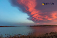 Lenticular clouds turn red at sunrise at Freezeout Lake WMA near Choteau, Montana, USA