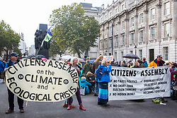 London, UK. 7 October, 2019. Climate activists from Extinction Rebellion carry banners calling for a Citizen's Assembly as they block Whitehall on the first day of International Rebellion protests to demand a government declaration of a climate and ecological emergency, a commitment to halting biodiversity loss and net zero carbon emissions by 2025 and for the government to create and be led by the decisions of a Citizens' Assembly on climate and ecological justice.