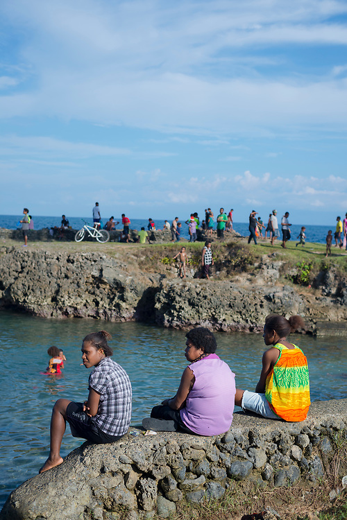 Three ladies sit on a wall beside a popular swimming spot on the coast of Madang, Papua New Guinea.