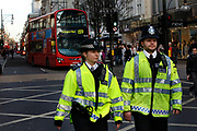 Police monitoring a student Demonstration which closes Oxford Street in London. Young people protest against many different government policies at this demonstration which included a sit down protest blocking Oxford Circus.