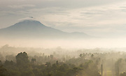 Mist rising from the forest, The Volcano Merbabu shrouded in clouds, Borobudur, Kedu Valley, South Central Java, Java, Indonesia, Southeast Asia