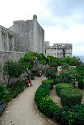 Formal garden in what was once a moat surrounding Dubrovnik old town, with Fortress Bokar in distance. Dubrovnik, Croatia