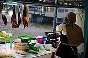 Woman prepares a meal in here restaurant food kiosk, Java, Indonesia.
