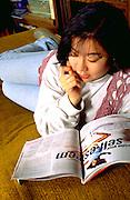Korean American woman age 28 taking magazine quiz.  St Paul  Minnesota USA