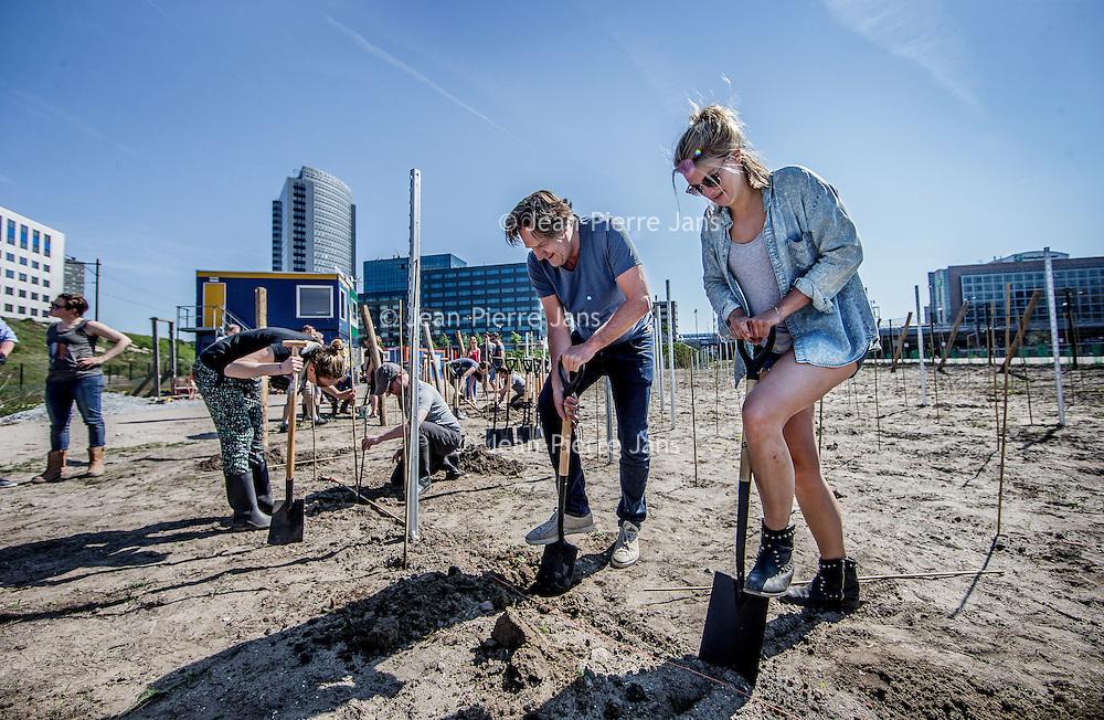"""Nederland, Amsterdam, 7 mei 2016.<br /> Startsein van planten  eerste wijnstokken bij Sloterdijk.<br /> Altijd al gedroomd van een wijngaard maar de stad nog niet kunnen loslaten? Zelf wijn willen maken en niet weten waar te beginnen? Wil je de stad groener, leefbaarder en mooier maken? Of wil je lekker actief bezig zijn in de natuur met anderen? Zomaar wat redenen om je aan te sluiten bij de Amsterdamse Stadswijngaard Wijn van Bret.<br /> Wijn van Brette Sloterdijk biedt ruimte aan 70 enthousiaste wijnliefhebbers.<br /> Je kunt meedoen door per oogst 10 wijnstokken te leasen voor Euro 225,-. Deze wijnstokken zullen ongeveer 10 flessen wijn opleveren. De wijnstokken zullen in Mei 2016 worden aangeplant.Na de oogst (voor de huidige inschrijvers in 2018) worden je druiven geperst, vergist, bewaard en uiteindelijk neem je je eigen flessen wijn mee naar huis. Je kunt je stukje wijngaard laten onderhouden, maar ook meehelpen met alle stappen die nodig zijn om tot een goede wijn te komen zoals het bijhouden van de grond, de """"groene oogst"""", en de oogst van de druiven zelf. Je maakt in ieder geval het grandioze oogstfeest mee en je naam wordt vermeld in de """"Hall of Bret"""" (Wijn van Bret – Hall of Fame). Je kunt na een cursus wijnmaken ook zelf actief meedoen met het vinificeren van de wijn; onder begeleiding van ervaren wijnmakers zal het vinificatie proces worden uitgevoerd. <br /> <br /> <br /> <br /> Foto: Jean-Pierre Jans"""