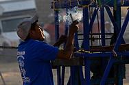 Un pirotécnico enciende una mecha en su participación en el concurso Castillos de Día, del la Feria Internacional de la Pirotécnia 2020.  /  A pyrotechnician lights up a fuse as he participates in the Pyrotechnics International Fair 2020.