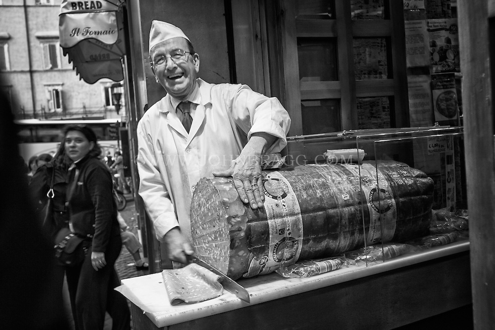 Butcher in Rome, Italy laughing while slicing a huge piece of mortadella.