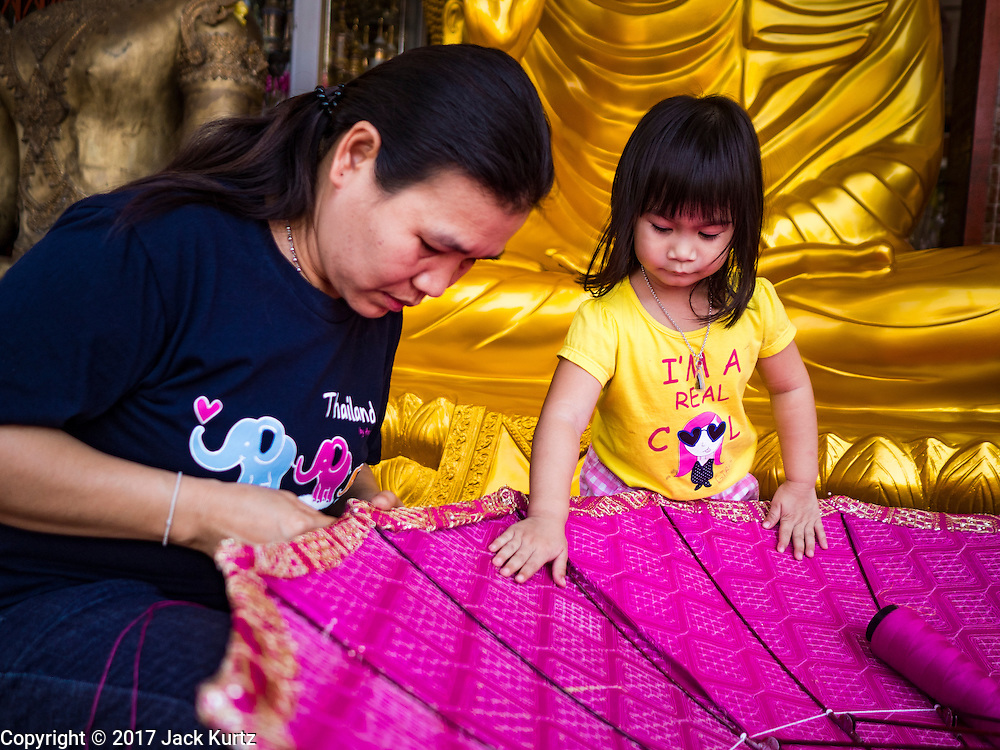 01 FEBRUARY 2017 - BANGKOK, THAILAND: A girl and her mother work on a large traditional parasol at a shop that makes and sells Buddhist paraphernalia in Bangkok. The umbrellas are used as parasols to keep the sun off important Buddha statues and at formal events. In Thai culture, the parasols were used to provide shade for members of the royal family or representatives of the royal family.     PHOTO BY JACK KURTZ