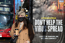 © Licensed to London News Pictures. 25/01/2021. London, UK. A woman wearing a protective face covering stands next to the government's 'Don't Help The Virus Spread' publicity campaign poster at a bus stop in north London. Prime Minister Boris Johnson is set to approve plans for Australia-style hotel quarantines for anybody returning from abroad, who will have to spend ten days isolating in a hotel at their own expense. Photo credit: Dinendra Haria/LNP