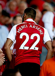 An Arsenal fan in the stands wears a shirt honouring outgoing manager Arsene Wenger