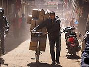 06 MARCH 2017 - KATHMANDU, NEPAL: A porter makes deliveries by bicycle in Kathmandu.      PHOTO BY JACK KURTZ