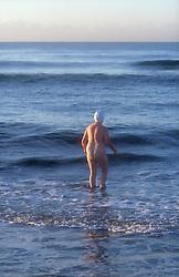Naked woman entering the sea at Maspalomas; Gran Canaria; Canary Islands; Spain,