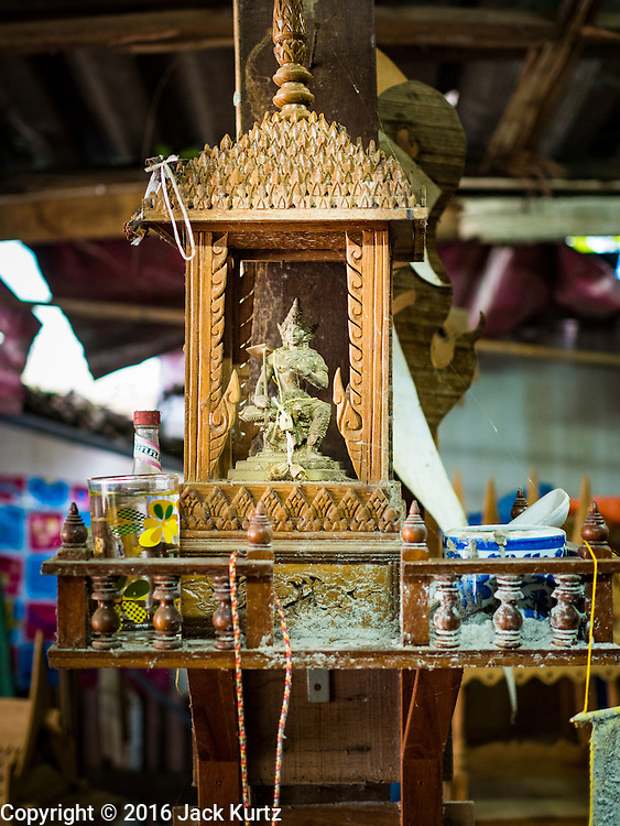 02 NOVEMBER 2016 - BANGKOK, THAILAND:  A spirit house in the family workshop. There used to be 10 families making traditional spirit houses out of teak wood in Ban Fuen, a community near Wat Suttharam in the Khlong San district of Bangkok. The area has been gentrified and many of the spirit house makers have moved out, their traditional wooden Thai houses replaced by modern apartments. Now there is just one family making the elaborate spirit houses. The spirit houses are made by hand. It takes three days to make a small one and up to three weeks to make a large one. Prices start at about $90 (US) for a small one. The largest, most elaborate ones can cost over $1,000 (US). Almost every home and most commercial buildings in Thailand have a spirit house, which is a shrine to the protective spirit of a the land. Spirit houses are also common in Burma, Cambodia, and Laos.       PHOTO BY JACK KURTZ