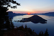 The rising sun clears the eastern caldera rim of Crater Lake, Oregon. Wizard Island, a dormant volcanic cone formed after the cataclysmic eruption of the ancient Mount Mazama, is visible near the center of the image. Crater Lake, protected as a national park, is the deepest freshwater lake in North America.