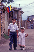 A young boy and his baby sister go for a walk from their temporary shelter after the Armenian Earthquake in Colombia, 1999.