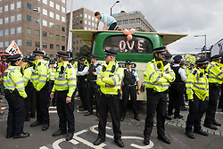 Metropolitan Police officers form a cordon around a vintage bus used by Extinction Rebellion activists to block a road junction to the south of London Bridge on the ninth day of their Impossible Rebellion protests on 31st August 2021 in London, United Kingdom. Extinction Rebellion are calling on the UK government to cease all new fossil fuel investment with immediate effect.