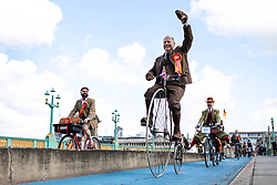 © Licensed to London News Pictures. 04/05/2019. London, UK. A man raises his hat as he cycles a Penny Farthing across Southwark Bridge on the Tweed Run bike ride in Central London. The annual event sees hundreds of people cycle around the capital past various landmarks wearing vintage tweed outfits. Photo credit: Rob Pinney/LNP