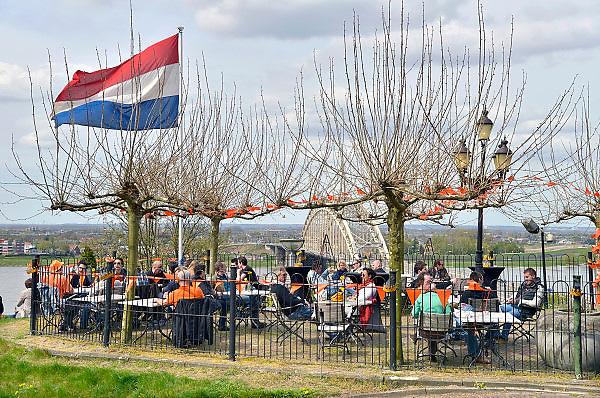 Nederland, Nijmegen, 30-4-2013, 30 aprilOp een terras aan het Hunnerpark, met uitzicht op de Waalbrug, genieten mensen van hun vrije dag. Op deze dag nam Koningin Beatrix afscheid en werd Prins Willem-Alexander koning.Foto: Flip Franssen