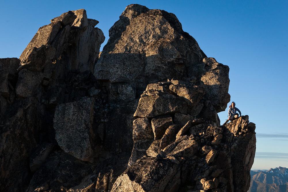 Kevin Steffa sits on a rock ledge below the narrow summit of Golden Horn, Okanogan National Forest, Washington.