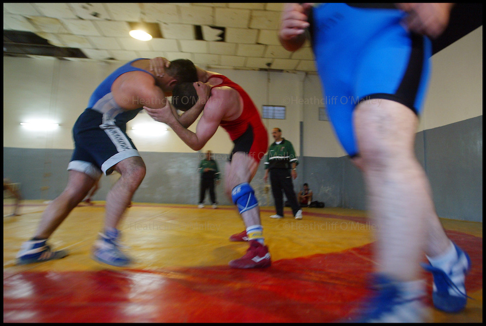 The Iraqi Olympic Wrestling Team train at the delapidated Aadamiyah Sports centre in Baghdad.Once brutalised by Saddam's son Uday Hussein who was previously head of the Olympic Committee in Iraq, the wrestlers now dream of a new life in the lucrative world of international sport.......Pic shows (right)Hassan Fardel,28,a freestyle wrestler who was tortured by Uday's Fedayeen,during a training session.