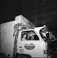 Two men sit in a truck by night while one other sleeps on the roof. Manila, Philippines, Asia