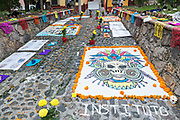 Dead of the Dead sand paintings on display outside the San Juan de Dios Church during the Dia de Muertos festival in San Miguel de Allende, Mexico. The multi-day festival is to remember friends and family members who have died using calaveras, aztec marigolds, alfeniques, papel picado and the favorite foods and beverages of the departed.
