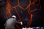 A graffiti artist painting a wall on the outskirts of Hanoi, Vietnam