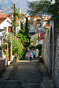 Two children (5 years old, 9 years old) walking down shady back-streets of Korcula, island of Korcula, Croatia.