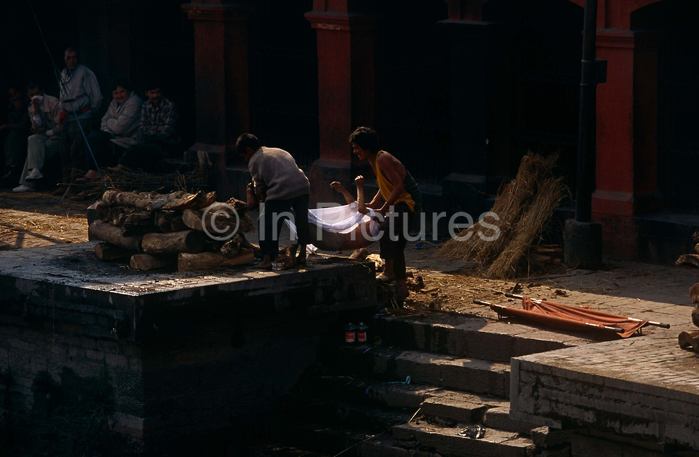 The family of a dead relative carry the body onto a pyre for a Hindu cremation at the Arya Ghat, Pashupatinath Temple. This is one of the most significant Hindu temples of Lord Shiva in the world, located on the banks of the Bagmati River in the eastern part of Kathmandu, the capital of Nepal. Arya Ghat, is the most widely used place of cremation in Nepal. Open-air cremations are held at the temple and non-hindu visitors may watch from outside. The temple is listed in UNESCO World Heritage Sites list