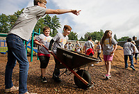 Mr. Lindberg guides his 4th grade students James and Logan as they spread mulch in the playground at Pleasant Street School during their United Way Day of Caring on Thursday morning.  (Karen Bobotas/for the Laconia Daily Sun)