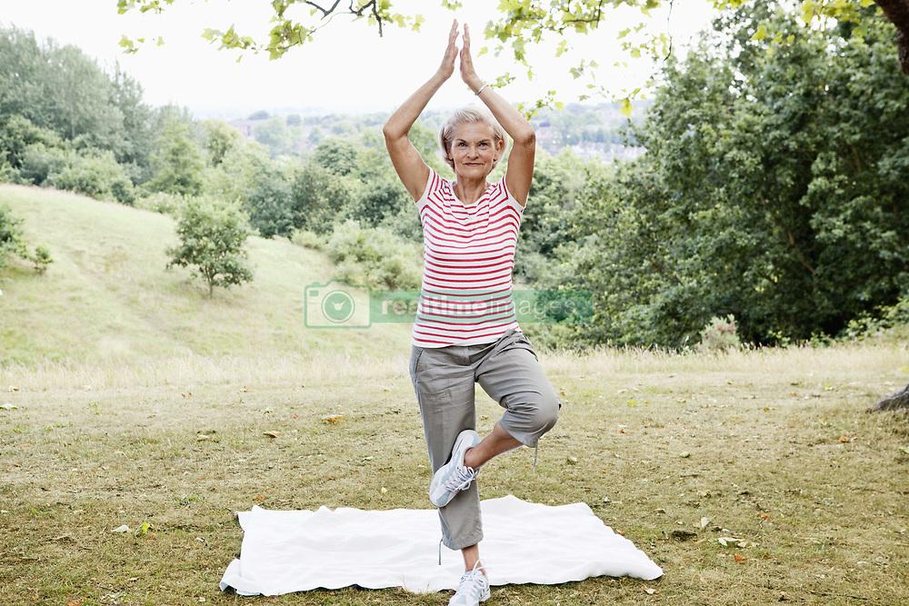 Jun. 28, 2010 - Mature woman strikes balancing pose. Model Released (MR) (Credit Image: © Cultura/ZUMAPRESS.com)