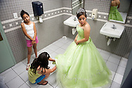 Maria Lopez-Garcia, 15, right, of Lanham, gets dressed in the bathroom of the Langley Park Community Center with her sister, Yesenia Lopez, 11, and mother, Leticia Garcia who wants her three U.S.-born children to have the careers she and her husband didn't have, to get out of poverty and live a comfortable life.  Lopez-Garcia is a legal resident, but her father has had immigration problems and was almost deported several years ago.  Lopez-Garcia celebrated her fifteenth birthday with a group of other Latinas from from low-income immigrant families taking part in a self improvement program.  It ended with a big quinceanera celebration marking the traditional end of childhood for these Hispanic girls.  <br /> (photo by Sarah L. Voisin/The Washington Post)