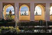 A young man looks out from under an archway at sunset in the Patio de la Acequia in the Generalife complex, La Alhambra, Granada, Andalusia, Spain.