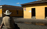 Man sitting at a crossroads in Antigua, a UNESCO World Heritage Site in Guatemala