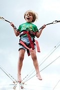 """Boy/girl """"fly/ride"""" on the bungee trampoline at Mountain Village Heritage Plaza, Telluride Village, Colorado, USA"""