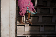 A woman is walking out of the Taj Mahal main area on stair reinforced with wood planks in order to avoid damage to the already poor Markana marble, in Agra.