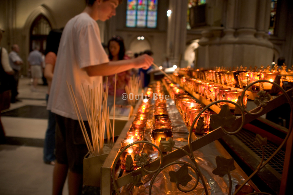 young man lighting a candle in St. Patricks cathedral NYC