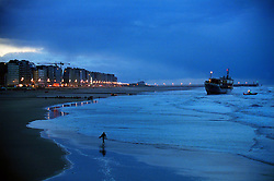 """BLANKENBERGE, BELGIUM - NOVEMBER 9, 2001 - A surfer calls it a day as night falls on the German cargo ship """"Heinrich Behrmann"""", which was beached by heavy seas after losing power to the main engine late Thursday night at Blankenberge. The ship was heading for the port at Zeebrugge from Ireland, and was carrying dry cargo, none of which was hazardous. The salvage company Unie Van Redding - En Sleepdienst N.V. was hired to free the ship, but had to wait for the high tide. Three unsuccessful attempts were made Friday, the second attempt resulted in the injury of two workers when tug boat cables snapped. The beached ship has attracted the attention of curious tourists. (Photo © Jock Fistick)"""