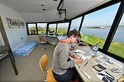 Nederland, Millingen, 21-4-2016Kunstenares Chris Ros zit in de voormalige telpost van rijkswaterstaat aan de Rijn, waal,  als artist in residence, en werkt aan een tekening . op deze plek zitten regelmatig kunstenaars die werken aan een gemeenschappelijke expositieFOTO: FLIP FRANSSEN