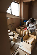Packing bottles of shochu at Nekka Shochu Distillery, Tadami, Fukushima, Japan, February 22, 2018. The Nekka shochu distillery was founded in July 2016 and at that time was the smallest shochu distillery in Japan. It makes shochu from locally-grown rice, and is helping support a local economy that has languished since the nuclear disaster of 2011.