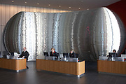 Greeting visitors to Ernst & Young's Norman Foster-designed 385,000 square foot European headquarter are a team of receptionists seated working at PC computers in front of a shining art work sculpture by MCM Architecture Limited. This is a scene of understated efficiency of a modern office environment. Four staff composing of three females and one man, look presentable and well-dressed to reflect the casual sincerity that E & Y portray to the world of accountancy and auditing whose 114,000 employees are in 700 locations across 140 countries around the world. They have currently invested in approximately 500,000 Pounds of office art.